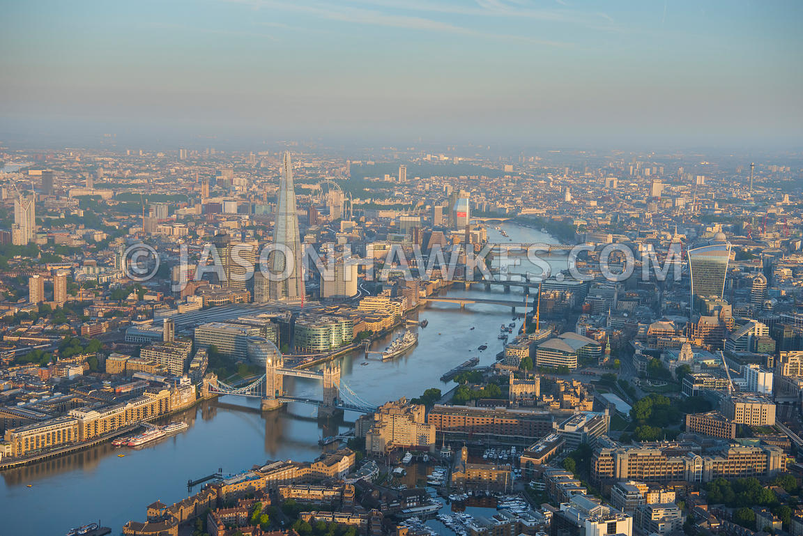 Dawn view from Tower Bridge and Tower of London looking West down River Thames.