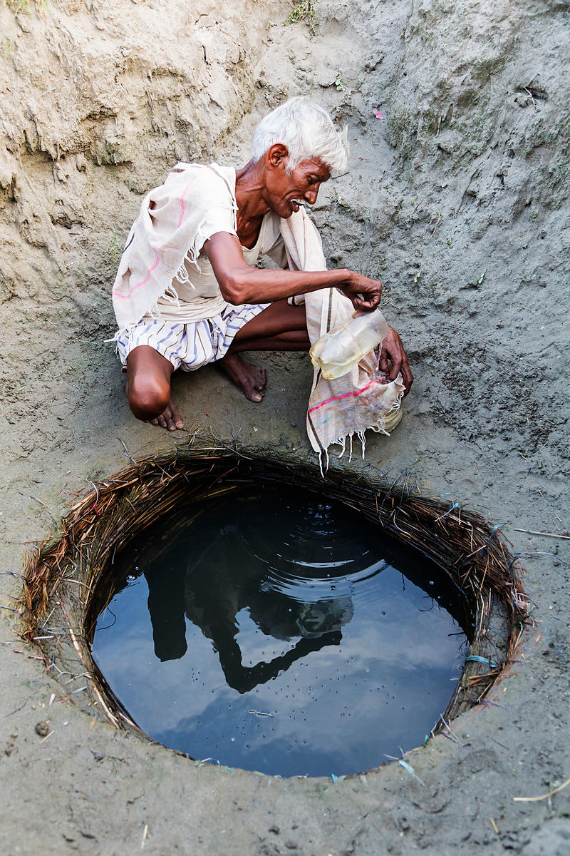 Man Filtering Water from a Homemade Well in the Yamuna River Floodplain
