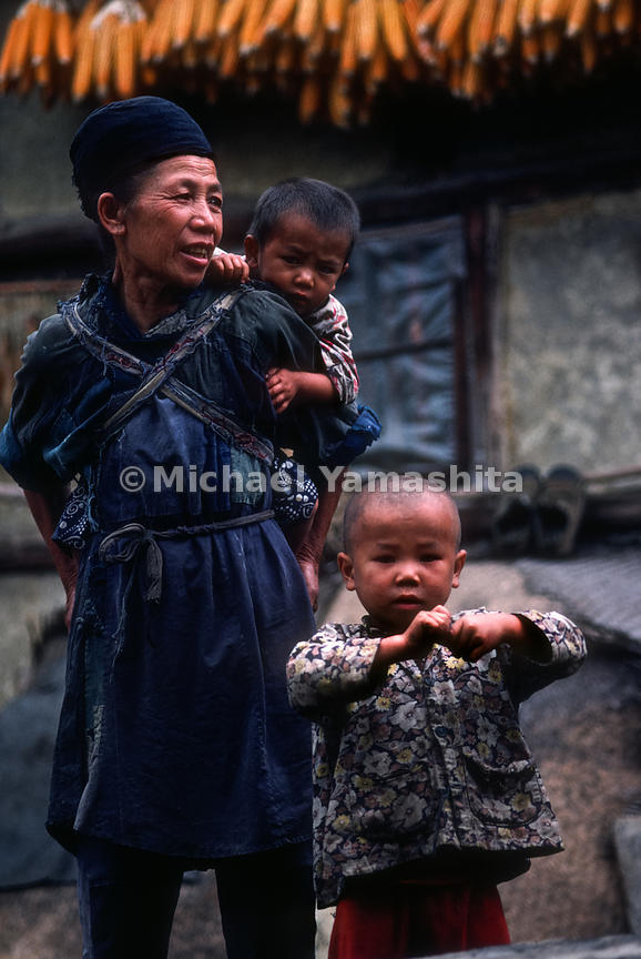 Portrait of a woman and two children in Buyi Village. Guiyang, Guizhou, China.