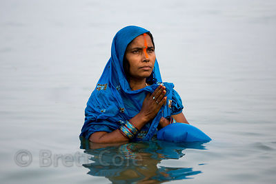A woman prays on the Ganges River during Chhath Puja, Varanasi, India. Chhath Puja is a devotion to the Sun God Surya in whic...