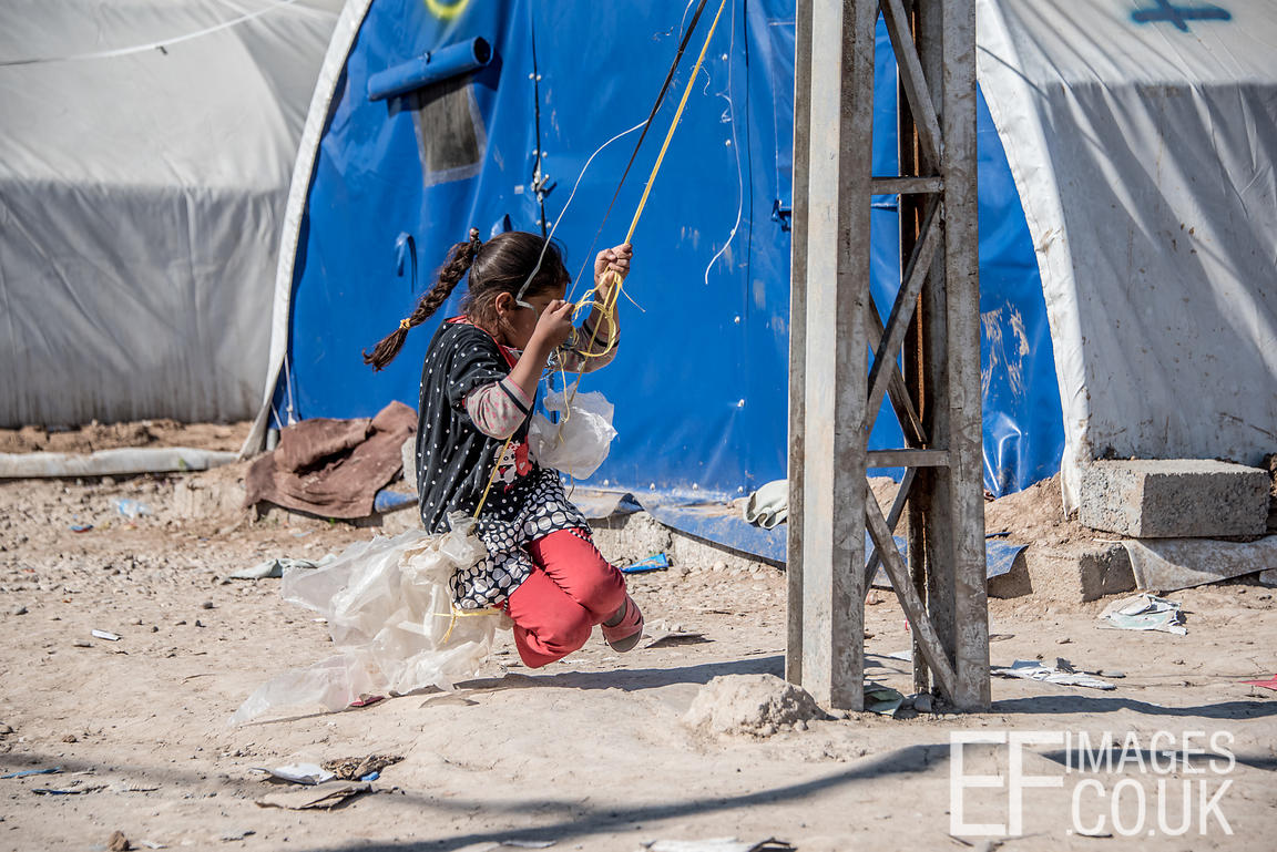 A Little Girl Resident Of The Hamam al Alil IDP Camp Near Mosul Plays On A Rope Swing Made From Electrical Cable And Plastic ...