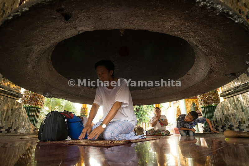 A man kneels in prayer beneath a bronze bell at Shwedagon Pagoda. The previous centerpiece bell at the pagoda - a reputedly 2...