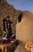 Woman baking bread in a traditional oven, Timbuktu, Mali