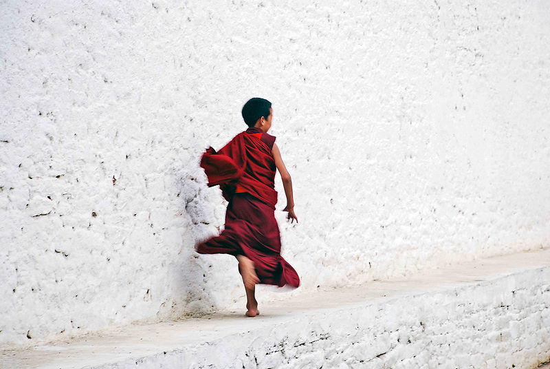 This photograph of a young buddhist monk running was shot in a monastery in Bhutan.