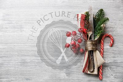 Table fork and knife set with napkin, christmas fir branch, red berries and napkin ring on gray wooden background copy space