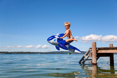 Boy jumping into lake with toy whale