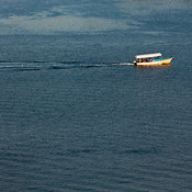 Small boat carring passengers crosses a bay of blue water, Mazatlán, Sinaloa, Mexico