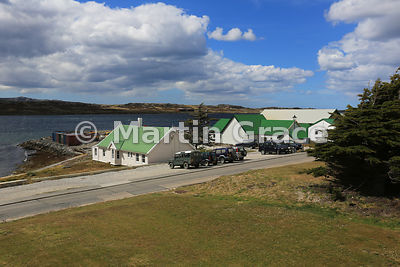Typical Falkland Islands buildings with corrugated roofs and cladded exterior, and four-wheel-drive vehicles parked outside, ...