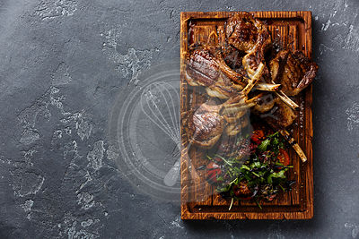 Grilled lamb ribs with tomatoes and arugula salad on cutting board on dark background copy space