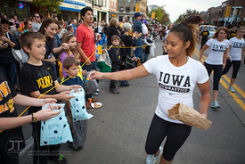 A member of the UI Gymnastics team hands out candy in the  University of Iowa homecoming Parade on Clinton St in Iowa City on...