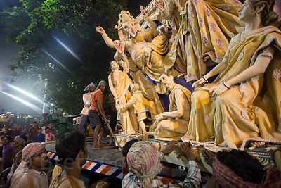 Hindu families immerse idols of the goddess Durga in the Hooghly River at night during the Durga Puja festival, Babughat, Kol...