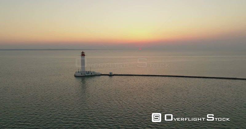 Drone flies over the tranquil waters of Odessa Port towards the Odessa Lighthouse. The sun is rising in the distance. Ukraine