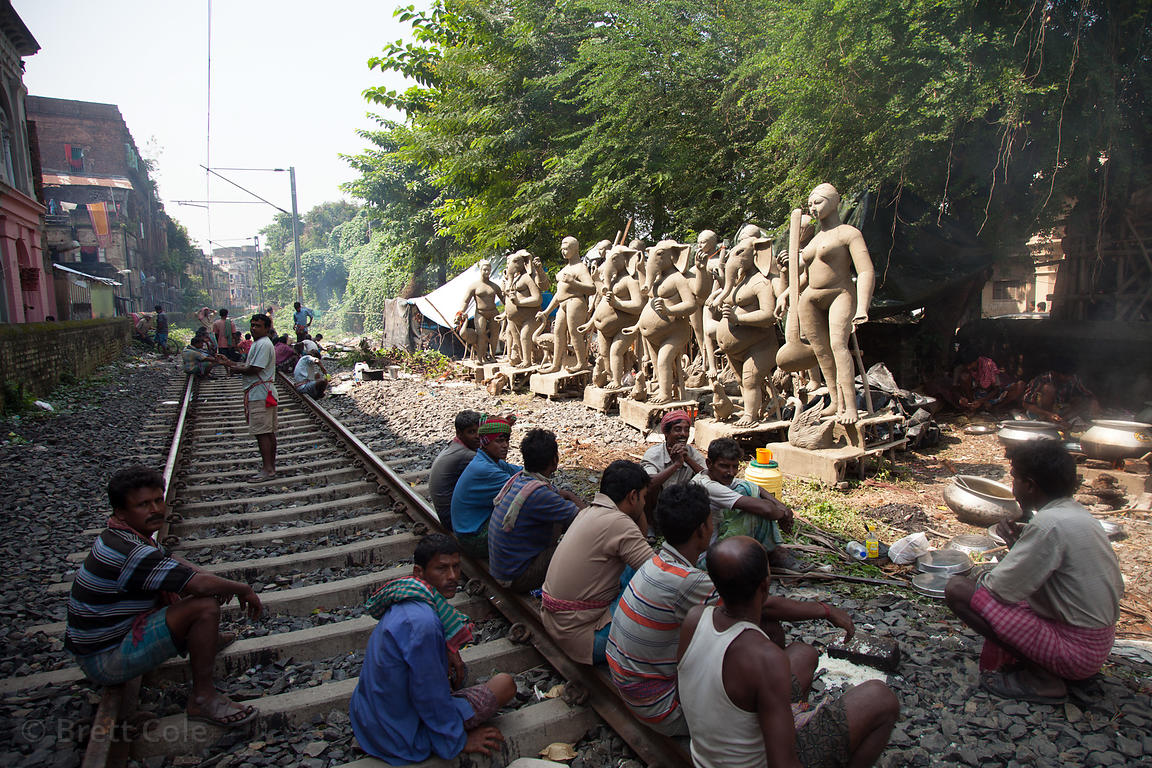 Clay Durga Puja idols dry along the railway tracks in Kumartoli (Potter's Town), Kolkata, India. The idols are sculpted from ...