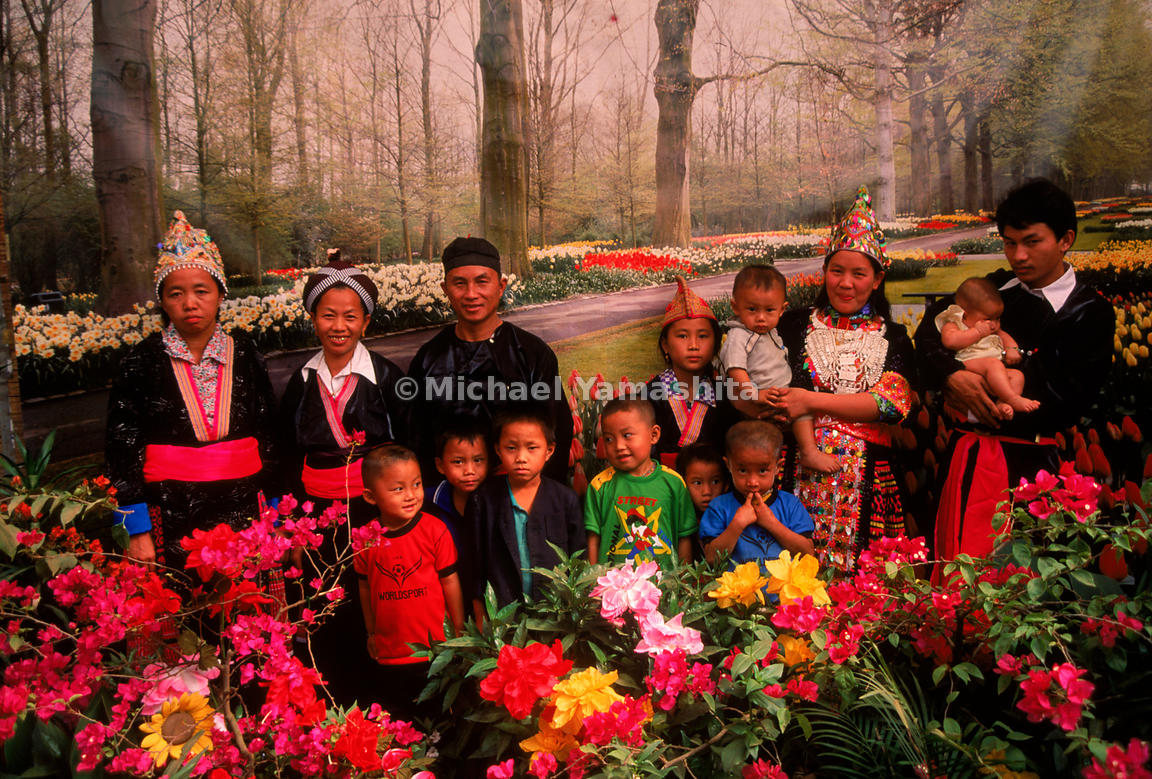 Their world rapidly changing around them, a displaced Hmong hill tribe family poses in traditional dress against a backdrop o...