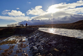 A hiker passing a fresh water reservoir in the English  Countryside, Muggleswick Common near Edmundbyers, England UK.