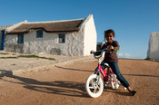 Girl riding her bicycle in the fishing village of Kassiesbaai at Arniston, South Africa