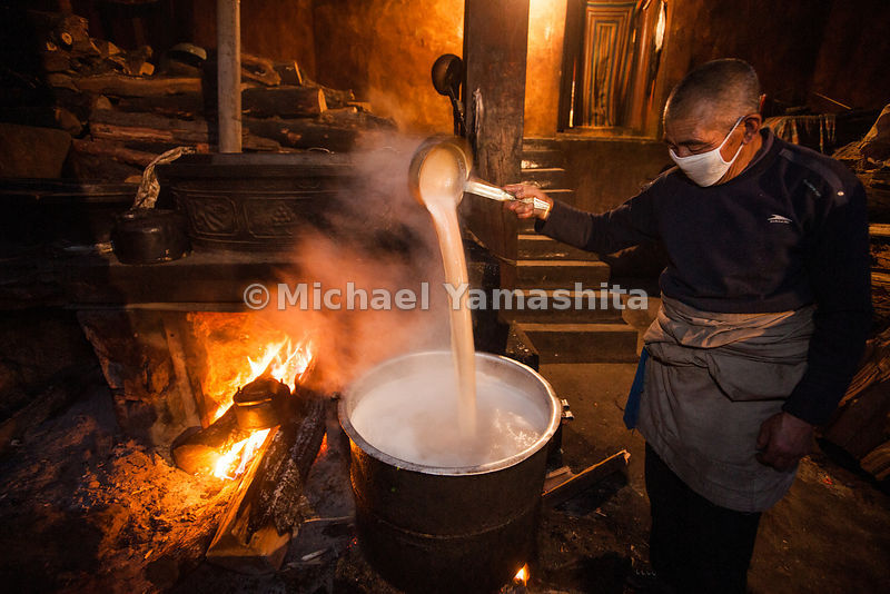 A monk prepares a steaming pot of yak butter tea at Garthar Monastery.