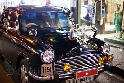 Black Ambassador car at night in Newmarket, Kolkata, India.