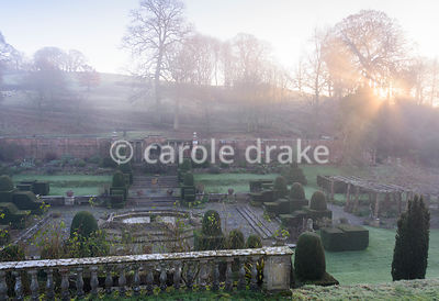 Winter sun dawns over the Fountain Court, laid out in the 1920s, at Mapperton, Dorset, with clipped yews, vine covered pergol...