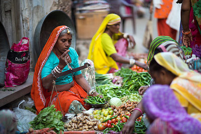 A woman weights peppers for a customer at a vegetable market, Pushkar, Rajasthan, India
