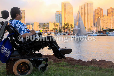 Man in a power wheelchair in a coastal park overlooking a city harbor during sunset