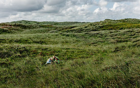 Danish father and daughters playing in the dunes in Thy