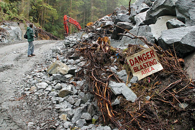 An activist stands in  a new logging road on Princess Royal Island, British Columbia, next to a sign reading Danger-Blasting ...