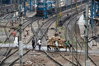 Workers push a load of baskets across railroad tracks at the Delhi Railway Station, Delhi, India