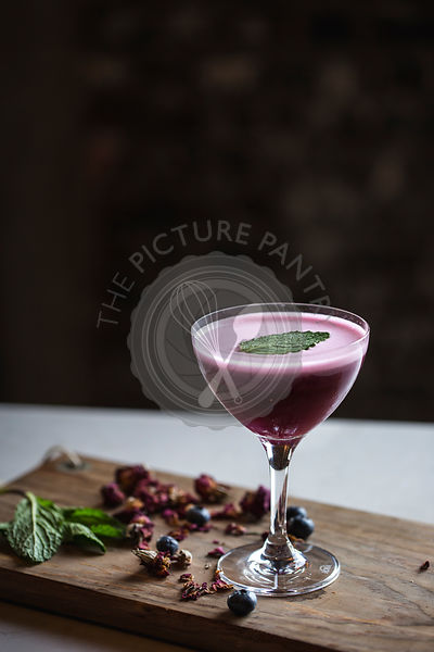 A coupe glass filled with blueberry cocktail