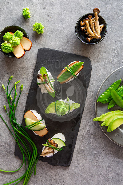 Vegan nigiri sushi and ingredients on white marble board over grey concrete background
