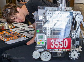 Jake Drahos, a senior at Muscatine High School, inspects a robot on display at the STEM Round Table Discussions. ?A Celebrati...