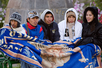 A group of college students huddle under a blanket while waiting to practice a dance routine for Cusco Week in Cusco, Peru (m...