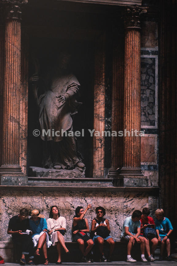 Visitors of the Pantheon sit in front of the colonnades on the outside. Rome, Italy, 1988.
