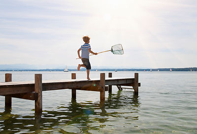 Boy running on dock with fishing net