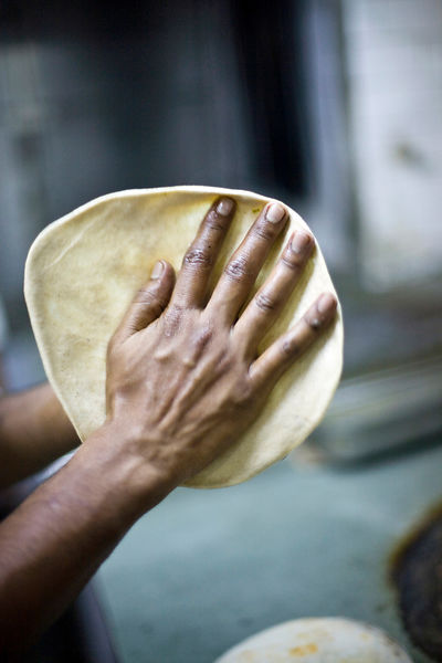 India - Delhi - A chef prepares chapati at the Village Restaurant
