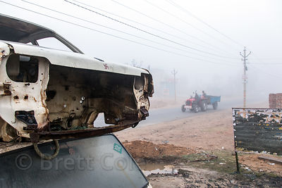 Tractor passes junk cars on a foggy winter morning in Tilora village, Rajasthan, India