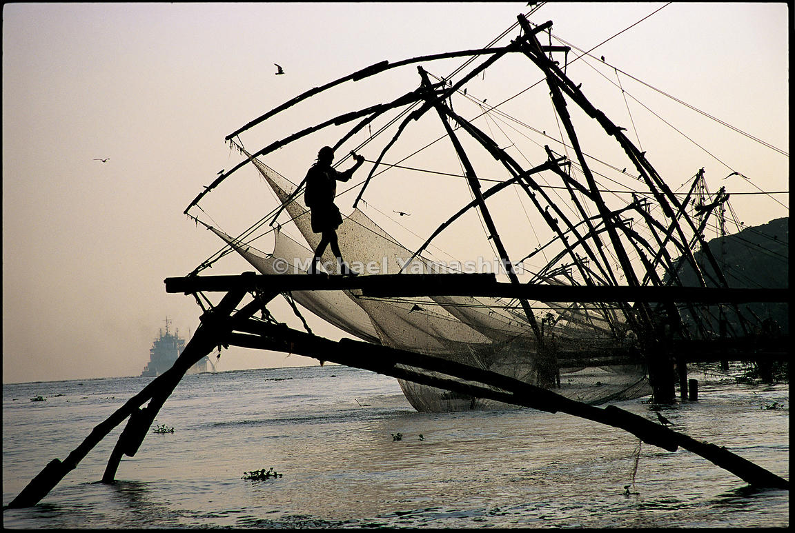 A fisherman balances on the frame of a dip net in Cochin. This Chinese fishing technique most likely came to Kerala in the 15...
