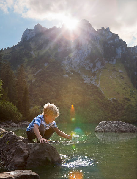 Boy dipping mug into still lake