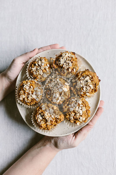 A woman is holding a plate full of freshly baked sweet potato muffins photographed from the top view.