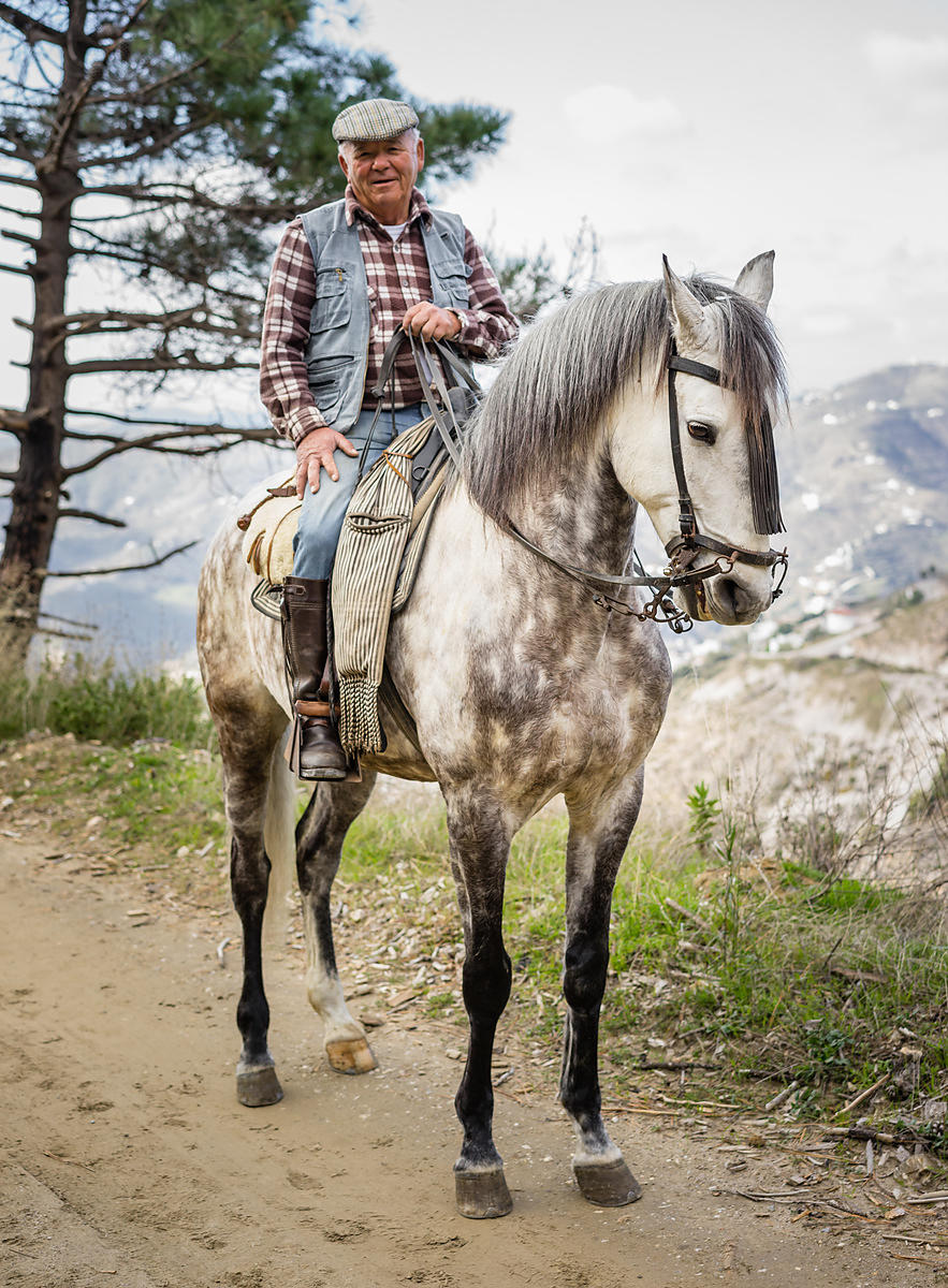Caballero riding in the mountains with piebald horse