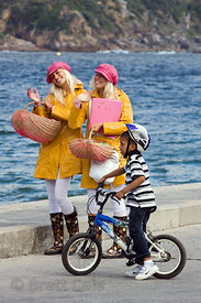 A boy riding his bicycle talks to Norwegian Twins who are raising money for college by entertaining tourists with song and da...