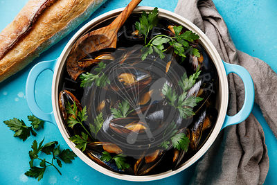 Mussels Clams in cooking pan with parsley on blue background close-up
