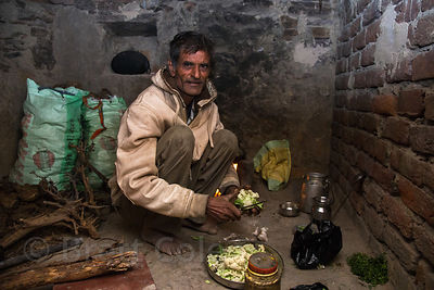 A man from the Cheeta caste prepares breakfast before sunrise on a freezng winter morning, Kharekhari village, Rajasthan, India