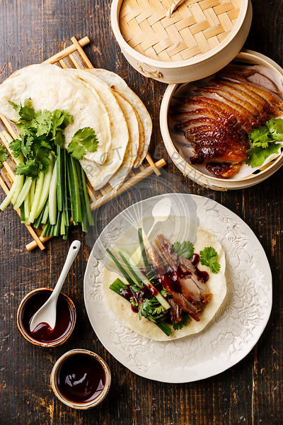 Peking Duck serving size with fresh cucumber, green onion, cilantro and roasted wheaten chinese pancakes with sauce Hoysin on...