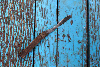 A fisherman's knife sits on a weathered board on a boat, Varanasi, India.
