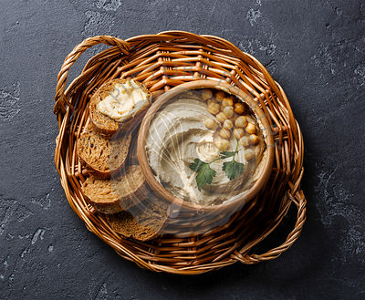 Homemade hummus and bread on wicker tray on black stone background