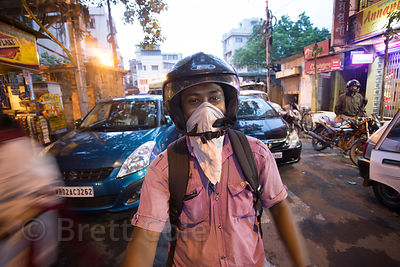 A man wears a bandana to protect against traffic fumes while on his motorcycle, Lake Gardens, Kolkata, India