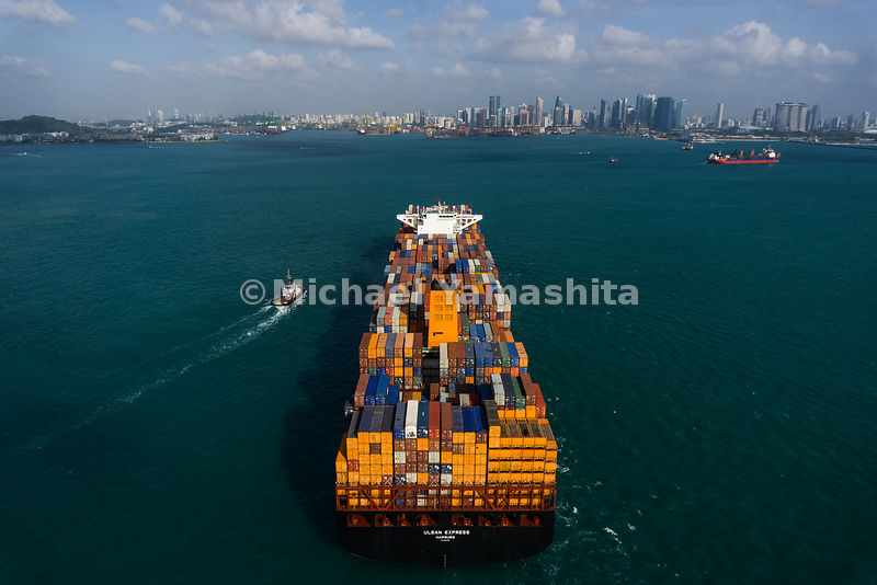 A tugboat races alongside a container ship heading toward the Port of Singapore.