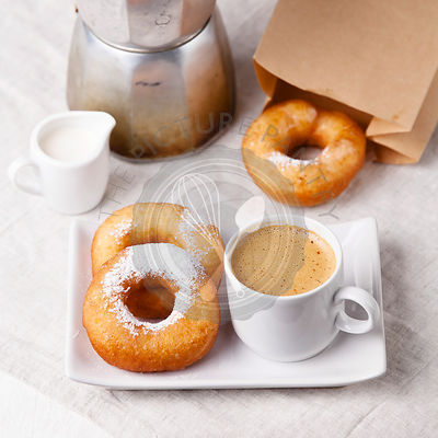 Donuts and coffee on morning breakfast table