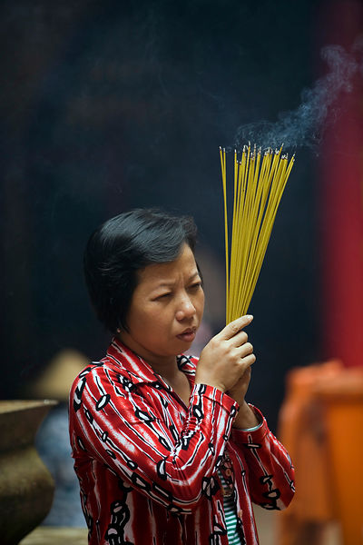 A woman lights incense at the Thien Hau Pagoda